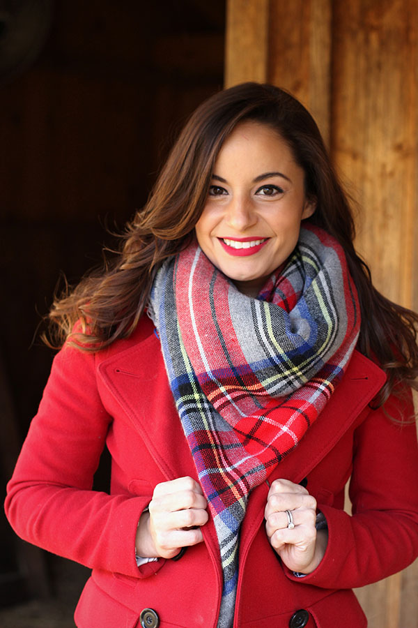 Brooke of Pumps and Push Ups wearing a black ASOS maternity dress with riding boots, tartan scarf and a red coat